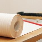 Eine Bürste, eine Tapetenrolle, ein Zollstock und ein Bleistift auf einem Tapeziertisch