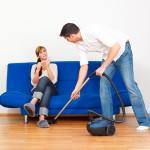 Mann Staubsaugt und Frau sitzt auf der Couch